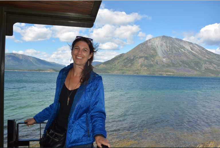 An image of a woman with brown hair smiling standing on a platform with a aqua body of water and mountain surrounded by clouds in the background.