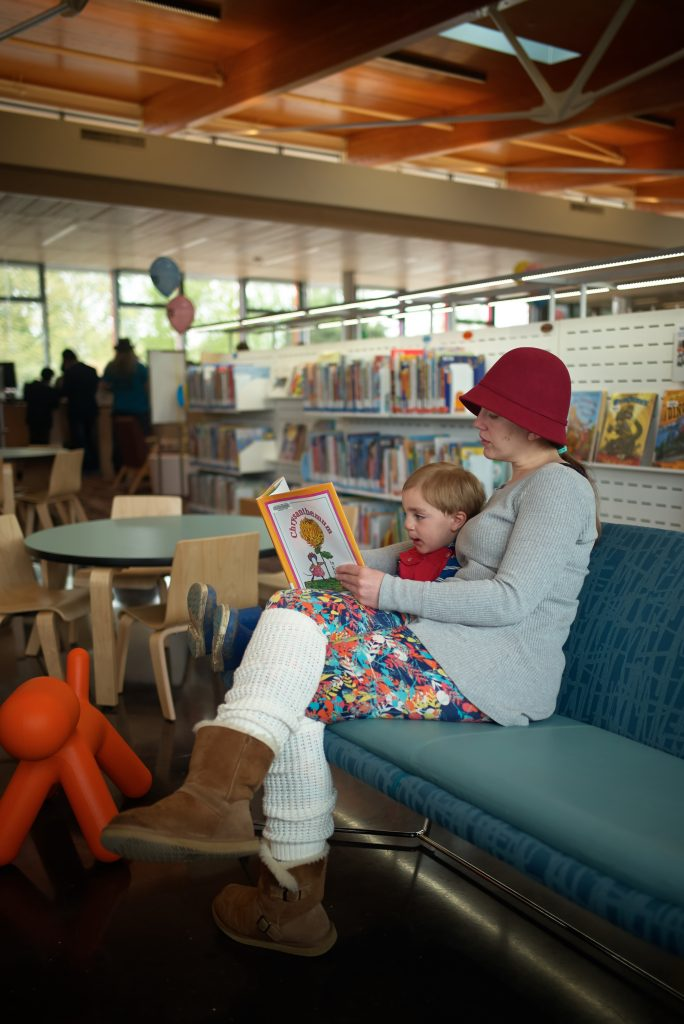 Mother reads with child during the grand open of Tukwila Library
